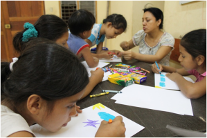 Pastora Yoli helps children at Fiel es Dios (Faithful is God) Lutheran Church in Iquitos, Perú, work on their daytime star pictures.